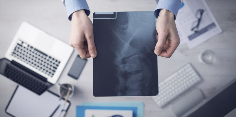 Medical X-ray, Radiologist, X-ray Image, Surgeon, Computer, Doctor, Desk, Directly Above, Human Spine, Examining, Stethoscope, Working, Clipboard, Medical Record, Equipment, Expertise, Technology, Healthcare And Medicine, Horizontal, Close-up, Human Bone, Illness, Medical Occupation, Holding, Laptop, Hospital, Protection, Adult, Physical Injury, Medical Exam, Lab Coat, Medical Clinic, Visit, Men